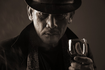 Portrait of mature aged gangster holding a glass of wine