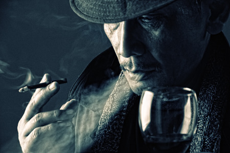 Close up face of tired old crime lord smoking a cigarette and drinking a glass of wine in the dark