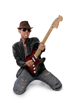 showmanship: Rock guitarist playing solo on his knees expressively, isolated on white background Stock Photo