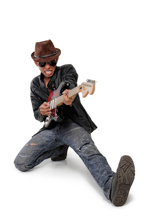 rock guitarist: Dramatic pose of young rock guitarist isolated on white background
