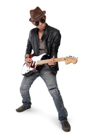 白い背景で隔離のエレク トリック ギターを演奏若い男のクールなポーズ
