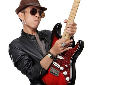 jazzy: Close up expression of a young man in leather jacket dark glasses and fedora hat playing solo on his electric guitar isolated on white background