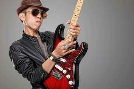 jazzy: Close up expression of a young man in leather jacket dark glasses and fedora hat playing solo on his electric guitar in HDR style image Stock Photo