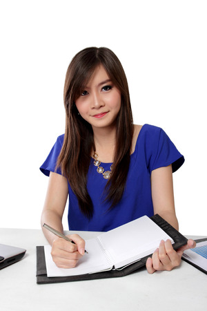 Happy young Asian woman sitting and writing on notebook, isolated on white background
