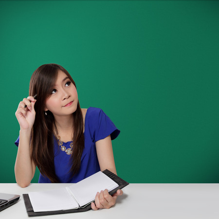 Beautiful Asian student girl looking up for idea while holding pen and notebook in front of green chalkboard background
