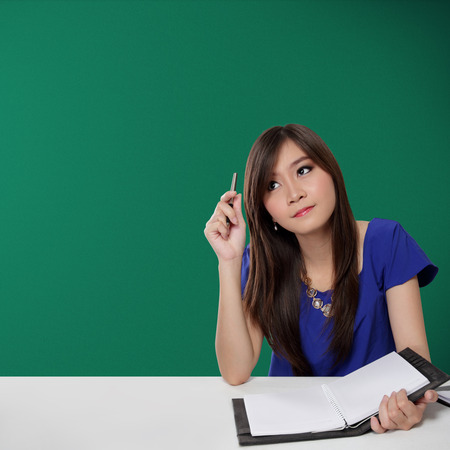 Pretty Asian student girl looking up for inspiration while holding pen and notebook in front of green chalkboard background