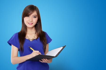 Young Asian woman holding pen and notebook, on vibrant blue background
