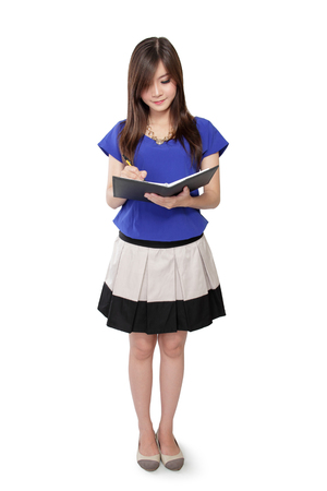 body writing: Full body of young Asian woman standing and writing on notebook, isolated on white background Stock Photo