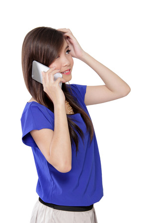 awkward: Young Asian woman scratching her head while talking on cell phone, with confused face and awkward smile, isolated on white background Stock Photo