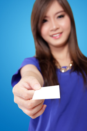 Beautiful young Asian woman handing a blank white card, on vibrant blue background