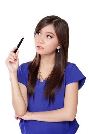 confundido: Hermosa adolescente asiática que sostiene una pluma mientras mira hacia arriba pensando para la idea con la cara confusa, aislados en fondo blanco Foto de archivo