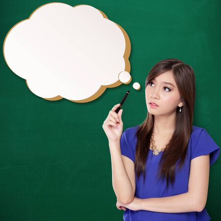 Beautiful Asian teenage girl staring imaginatively at a comic styled thinking bubble, on green textured background Stock Photo