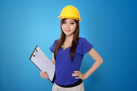 asian architect: Young Asian architect woman in yellow safety helmet holding work plan sheet, on vibrant blue background