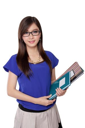 白い背景で隔離の本を保持している若いアジア女性の肖像画