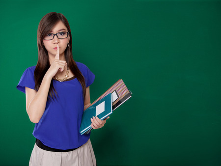 Young Asian lady  asking you to be quiet while holding books, on green chalkboard background