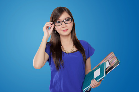 Young Asian teacher  woman adjusting her glasses frame while holding some books, on blue vibrant background