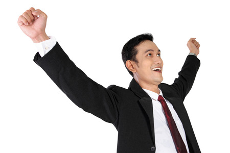 Young successful Asian businessman in suit and tie expressing happiness isolated on white background
