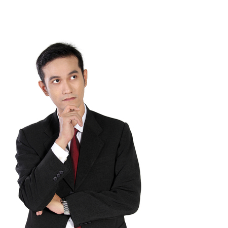 solver: Young Asian businessman looking up thinking while holding his chin with one hand isolated on white background Stock Photo