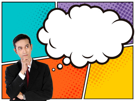 hand on chin: Business concept in comical style. Young Asian businessman looking up thinking to comic bubble above him while holding his chin with one hand on colorful panel background Stock Photo