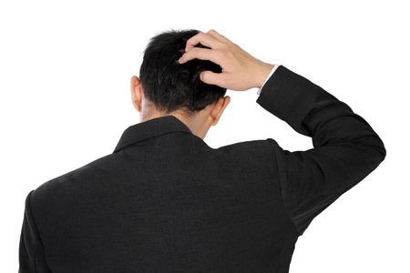 ストレスや白い背景で隔離する混乱を表現する彼の頭の背中を掻くフォーマルな服装の男