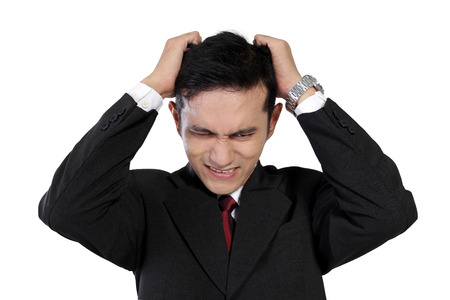 Close up of young Asian businessman pulling his hairs expressing stress and frustration isolated on white background photo