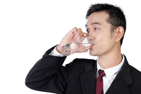 Close up portrait of young Asian businessman drinking a glass of water isolated on white background