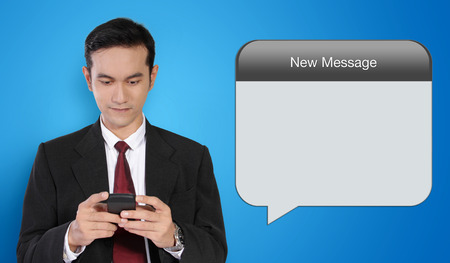 pending: Conceptual image of business and telecommunication. Image of young Asian businessman texting, and empty New Message bubble, isolated on stylish blue background