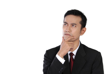 Young Asian businessman analyzing something up at copyspace in a pensive face expression,with one hand holding his jaw, isolated on white background photo