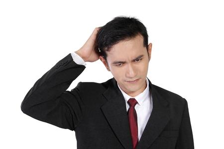若いアジア系のビジネスマンに孤立した白い背景、彼の頭を悩まの困惑している顔 写真素材