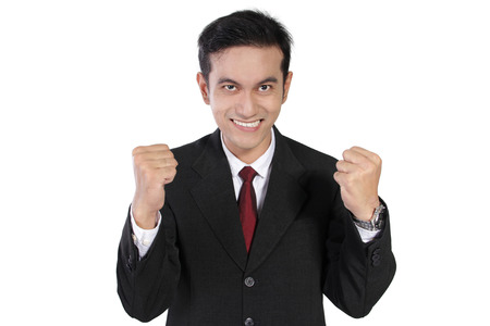 overly: Overly enthusiastic expression of young Asian businessman looking straight to camera with teeth and fists clenched, isolated on white background Stock Photo