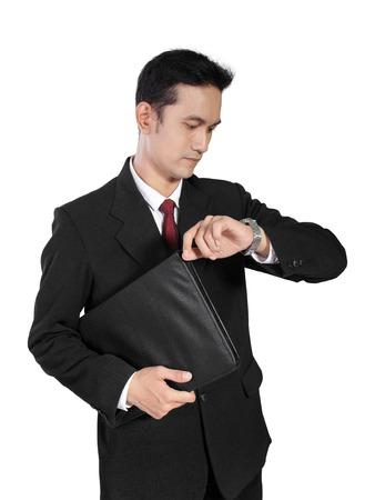 アジア男性事務員に立って、自分の時計を見て、イライラして、待っている白い背景で隔離