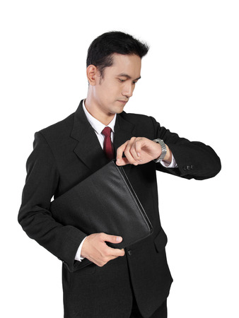 Asian male office worker standing, looking at his watch, waiting impatiently, isolated on white background