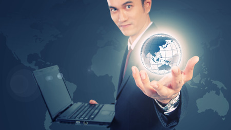 Conceptual image of internet information technology. Digital imaging of young man in formal suit holding laptop showing the world with his hands Stock Photo