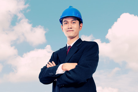 asian architect: Confident Asian architect in formal wear posing with crossed arms, on blue sky background. Conceptual image of leadership and reliability