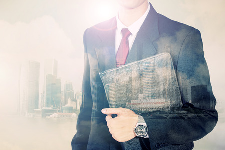Conceptual image of urban lifestyle. Double exposure of businessman body in suit and modern city horizon