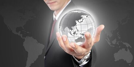 formal wear: The world is in your hand. Conceptual image of global control, power and domination. A man in formal wear holding a globe inside his hand