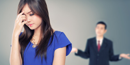 Conceptual situation image of a couple in business style having a fight. Female with stressful face as the foreground, and male with clueless expression as background