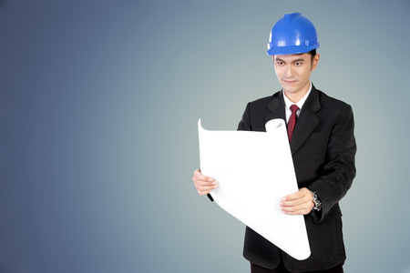 asian architect: Young Asian architect in blue safety helmet and formal suit opening and looking at paper scroll Stock Photo