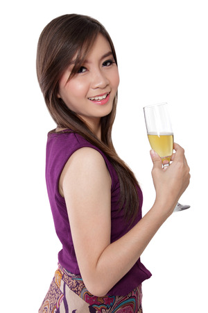 prom queen: Fresh looking Asian girl smiling to camera on her side while holding a glass of champagne, isolated on white background
