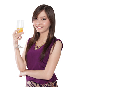 hedonism: Young luxurious Asian woman giving a nice smile to camera while holding a champagne glass, isolated on white background with copy space