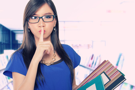geeky: Beautiful Asian librarian lady holding some books and asking for silence Stock Photo