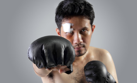 MMA fighter throwing a straight punch, on grey background Stock Photo