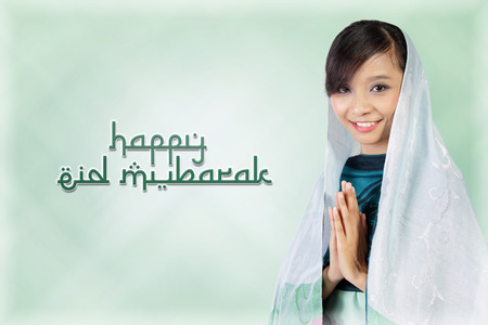 Happy Eid Mubarak. Composition of typography in Arabic style with image of smiling muslim woman over light green abstract background