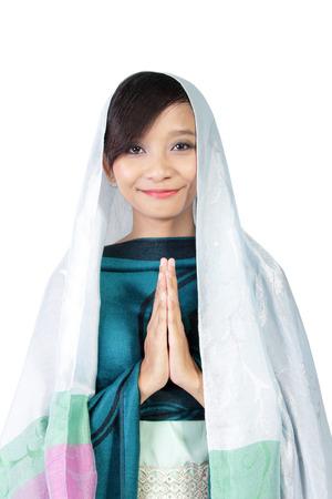 微笑对照相机的亚裔回教女孩以典雅的方式隔绝在白色背景