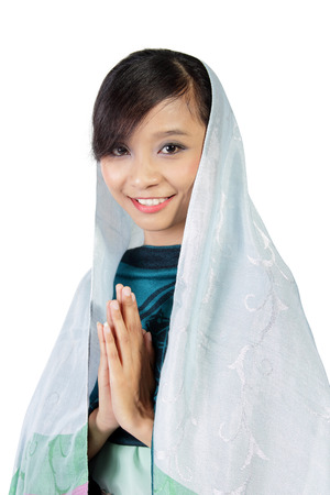 hijab: Young Asian muslim woman smiling to camera with praying hand gesture isolated on white background Stock Photo