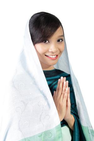 素敵なアジアのイスラム教徒の少女の白い背景に分離した宗教的なジェスチャーでカメラに笑顔