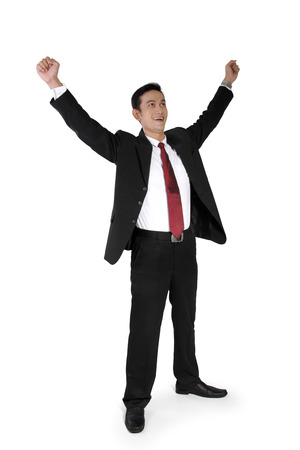 full shot: Full shot of attractive Asian businessman expressing victory, standing with both hands raised, isolated on white Stock Photo