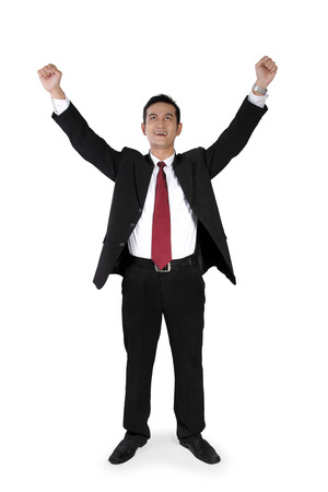 full shot: Full shot of attractive Asian businessman expressing happiness with both arms raised, standing perpendicular from the camera, isolated on white Stock Photo