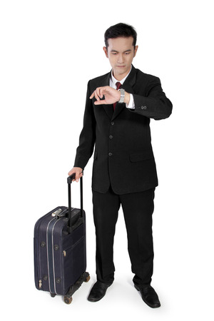 full shot: Full shot of attractive Asian businessman holding suitcase and checking on time, isolated on white background