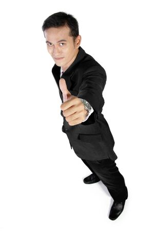 full shot: High angle full shot of young Asian businessman giving a thumb up to camera, isolated on white background